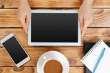 Girl hands with digital tablet and cup of coffee on a wooden table - 220071912