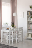 Real photo of dining room interior with chairs and white table with lavender and breakfast, window with drapes and rack with decor - 220099919