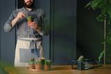 Man with gardening hobby exaggerating cacti in grey interior - 220099952