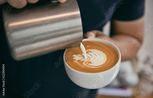 Barista making latte or Cappuccino with frothy foam, coffee cup in cafe.
