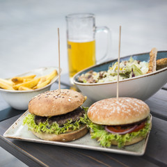 two sandwiches with salad and french fries with glass of beer on the table