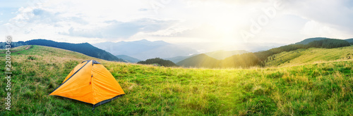Orange tent on meadow with green grass in mountains under bright