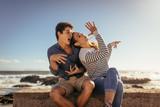 Couple having fun sitting on sea wall
