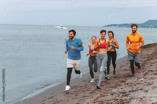 Group of young sports people running on the beach by the sea