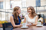 technology, lifestyle and people concept - happy young women with smartphones drinking coffee at cafe outdoors - 220107931