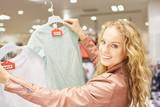 Junge Frau mit einer Auswahl von T-Shirts - 220109385