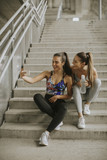 Two athlete women resting and taking selfie after jogging - 220116325