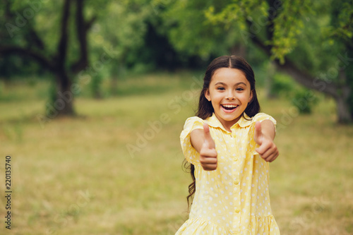 Fototapeta Sweet child showing thumbs up. Cute little girl in bright yellow polka dot summer dress smiling and showing thumbs up with both of her hands.