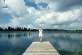 Back view of a blonde woman standing on wooden pier at the lake. Color tone filter effect used. - 220148562