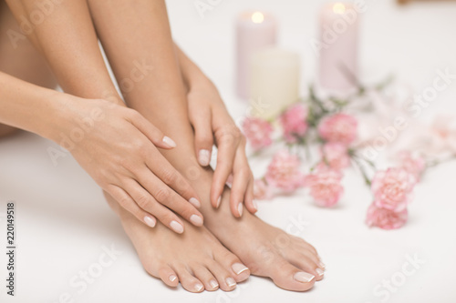 The picture of ideal done manicure and pedicure. Female hands and legs in the spa spot. - 220149518