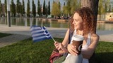 Beautiful female tourist in the park with the flag of Greece. - 220158160