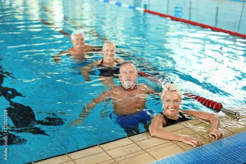 Sportive senior people in indoor swimming pool