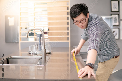 Young Asian man using tape measure for measuring granite countertops ...