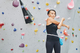 Pretty Vietnamese woman warming-up before bouldering on artificial wall - 220182922