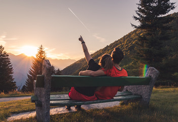 Couple sitting on bench in the mountains watching the sunset and a plane flying © NDStock