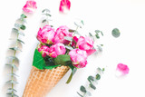 Creative flowers composition with waffle cone with pink roses and eucaliptus inside on white background. The concept of gift and celebration. Flat lay, top view.