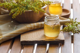Honey in glass jar with honey dipper on wooden table. Food ingredient and natural medicine concept.