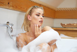 beautiful young blond woman taking a relaxing bath with foam - 220202728