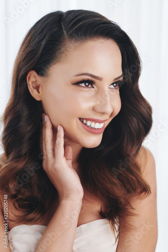 Portrait of beautiful pensive young woman with toothy smile