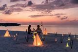 Romantisches Paar sitzt bei einem privatem Abendessen am tropischen Strand und genießt den Sonnenuntergang - 220217360