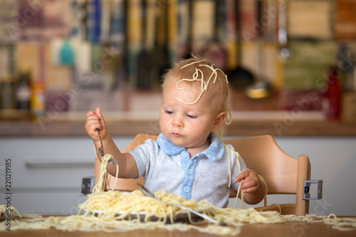 Little baby boy, toddler child, eating spaghetti for lunch and making a mess - 220219185