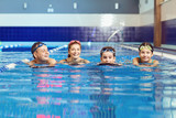A happy family is smiling in a swimming pool indoors. - 220224141