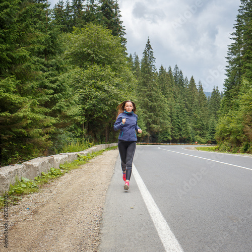 Young Smiling Woman Jogging On Mountain Road Happy Girl