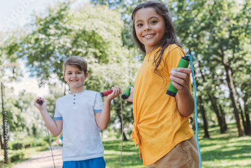 Wall mural adorable happy kids hiking skipping ropes and smiling at camera in park
