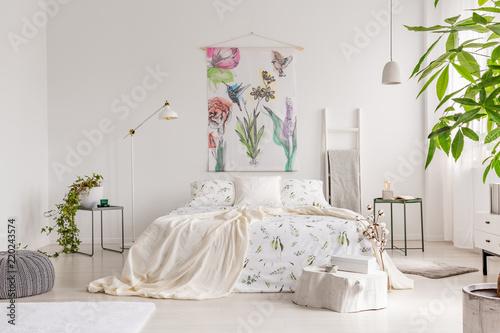 A bright eco friendly bedroom interior with a bed dresses in green plants pattern white linen. Fabric painted in flowers and birds on the background wall. Real photo. © Photographee.eu
