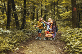 Mother and her little sons hiking trough forest .They learning about animal and plant life.