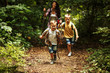 Mother and her little sons hiking trough forest .They learning about nature.