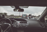 Driving a passenger car in traffic jam, view from inside on crowded road - 220246357