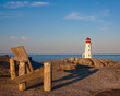 Wooden bench with Peggys Cove lighthouse in background on  sunny morning.