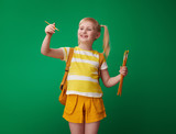 school girl drawing with brush in air on green background - 220247784