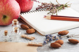 Empty notebook and pencils, apples