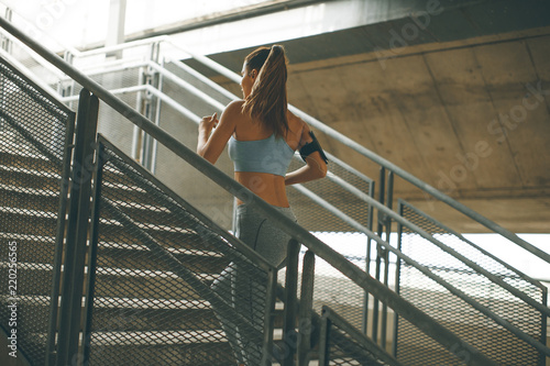 Wall mural Young woman running alone up stairs