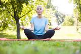 Senior woman in lotus pose sitting on green grass - 220256963