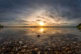 Sonnenuntergang an einem wunderschönen Steinstrand - 220258332
