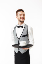 Young Joyful Waiter In Uniform Holding Tray  Cup Of Coffee In Hand While Happily Looking Aside Over   Sticker