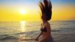 Leinwandbild Motiv Beautiful model in swimsuit posing on the beach in sunset sunlight with long hair making forms