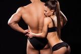 Sexy model hugging bodybuilder's back.