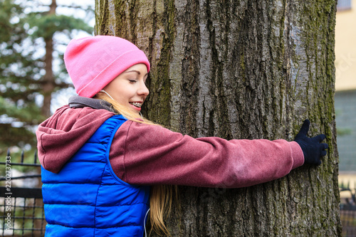 Woman wearing sportswear hugging tree - 220273733