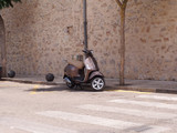 Parked scooter against a stone wall