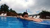 Happy, Teenage Girl Relaxing at Luxury Swimming Pool Edge - 220289910