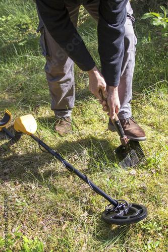 Mężczyzna kopie dziurę w ziemi za pomocą saperki. Poszukiwania militariów. Wykrywacz metalu leży na trawie obok.