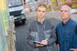 Men looking at load on lorry, holding clipboard