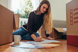 Woman sitting on floor and writing on paper - 220314581