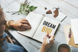 Woman writing Dream big on a notebook