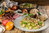 Pesto pasta with meat on a plate, a variety of cheeses and smoked meat and sausage, vegetables and spicy herbs on a wooden table. Close-up