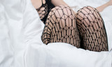 Knees of a woman in erotic underwear on a white bed.